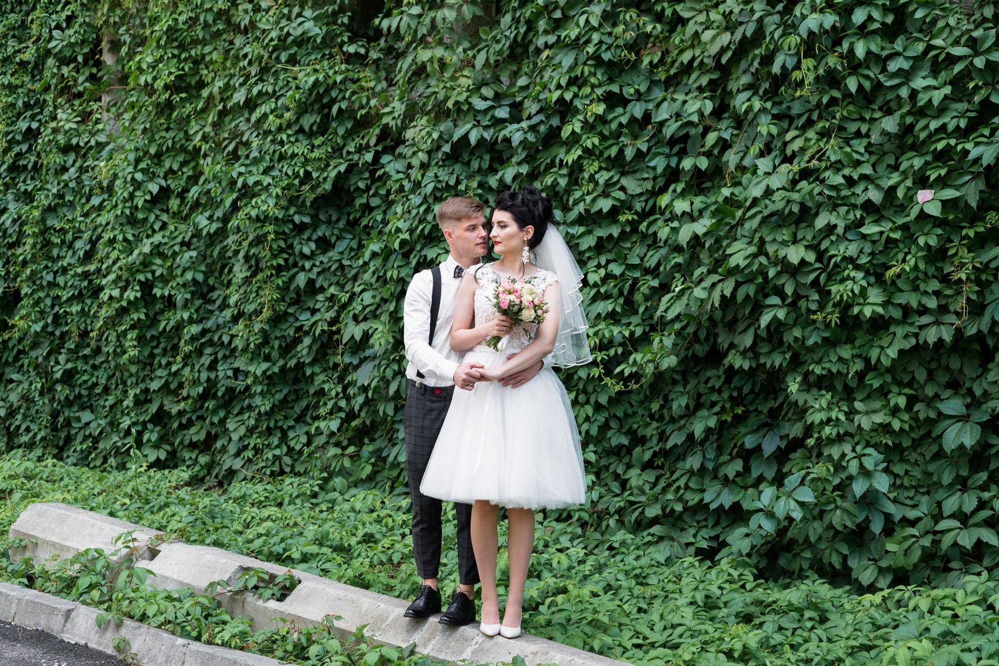 Свадебная фотосъемка в студии Плей - молодожены возле зеленой стены