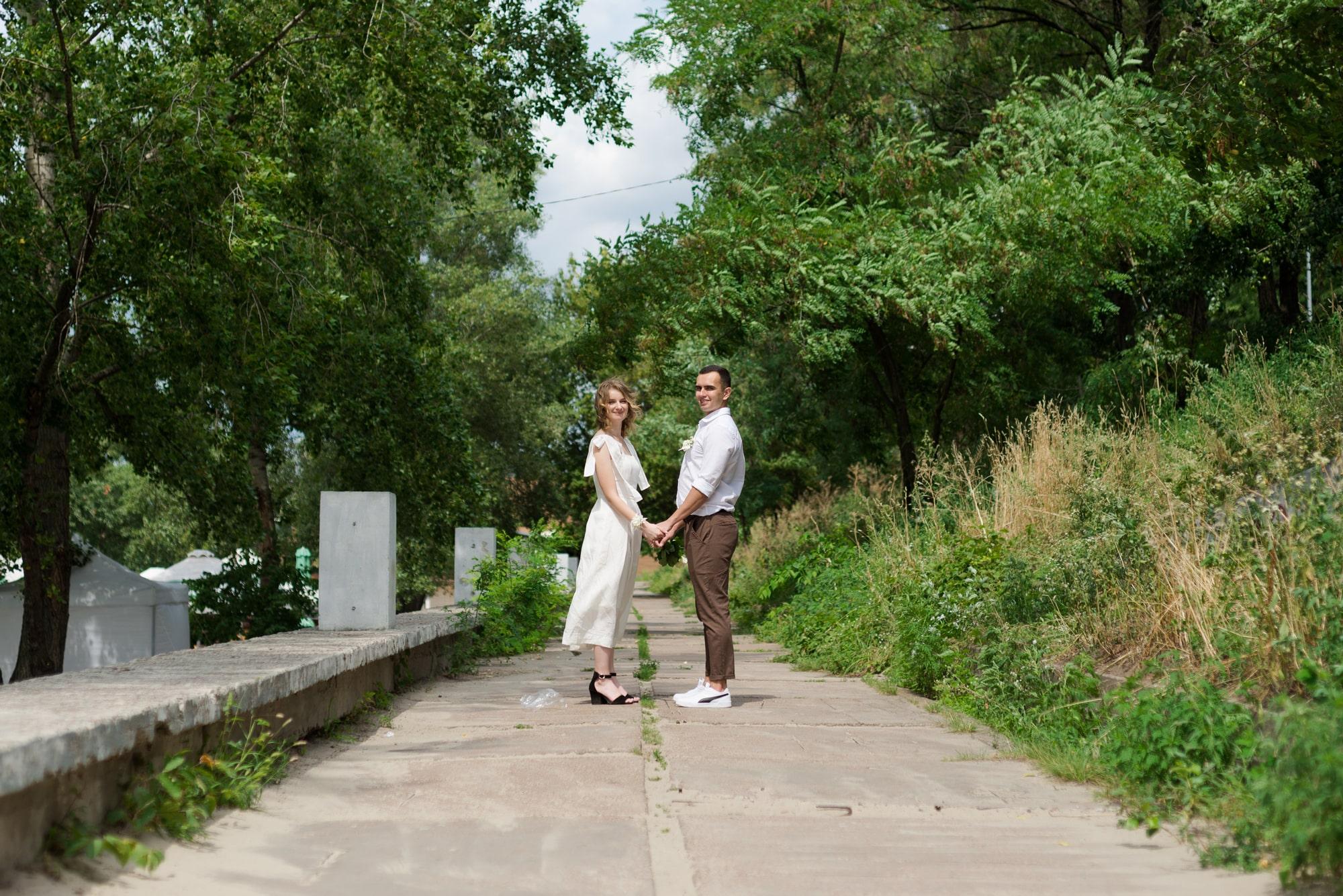 Фотосессия свадебная возле Днепра - молодожены гуляют держась за руки