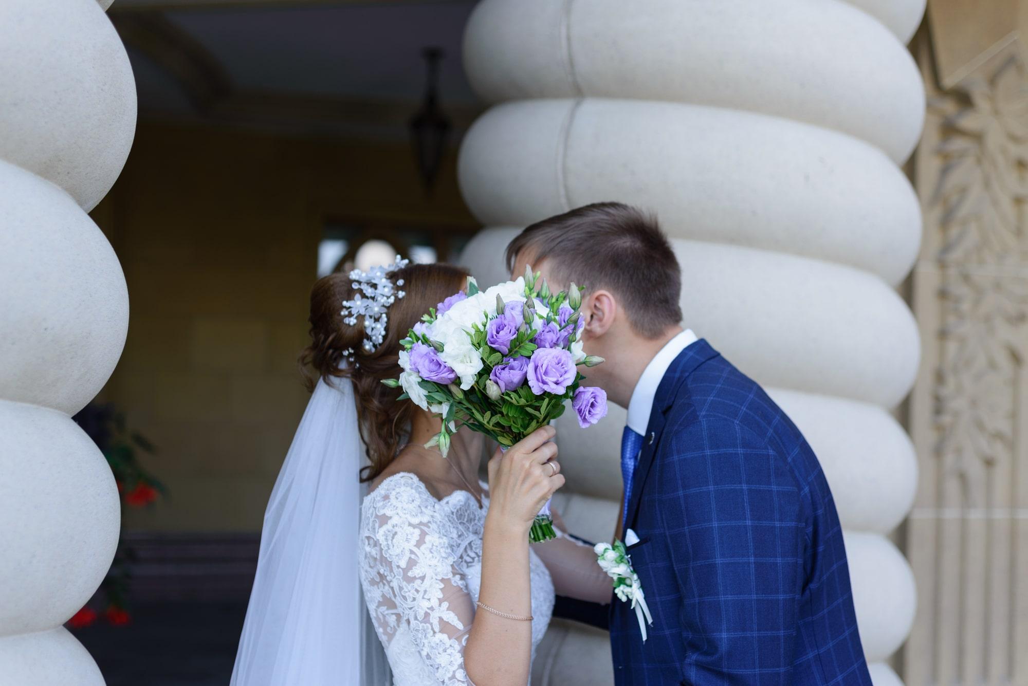 Свадебная фотосъемка в Межигорье - пара спрятала поцелуй за букетом