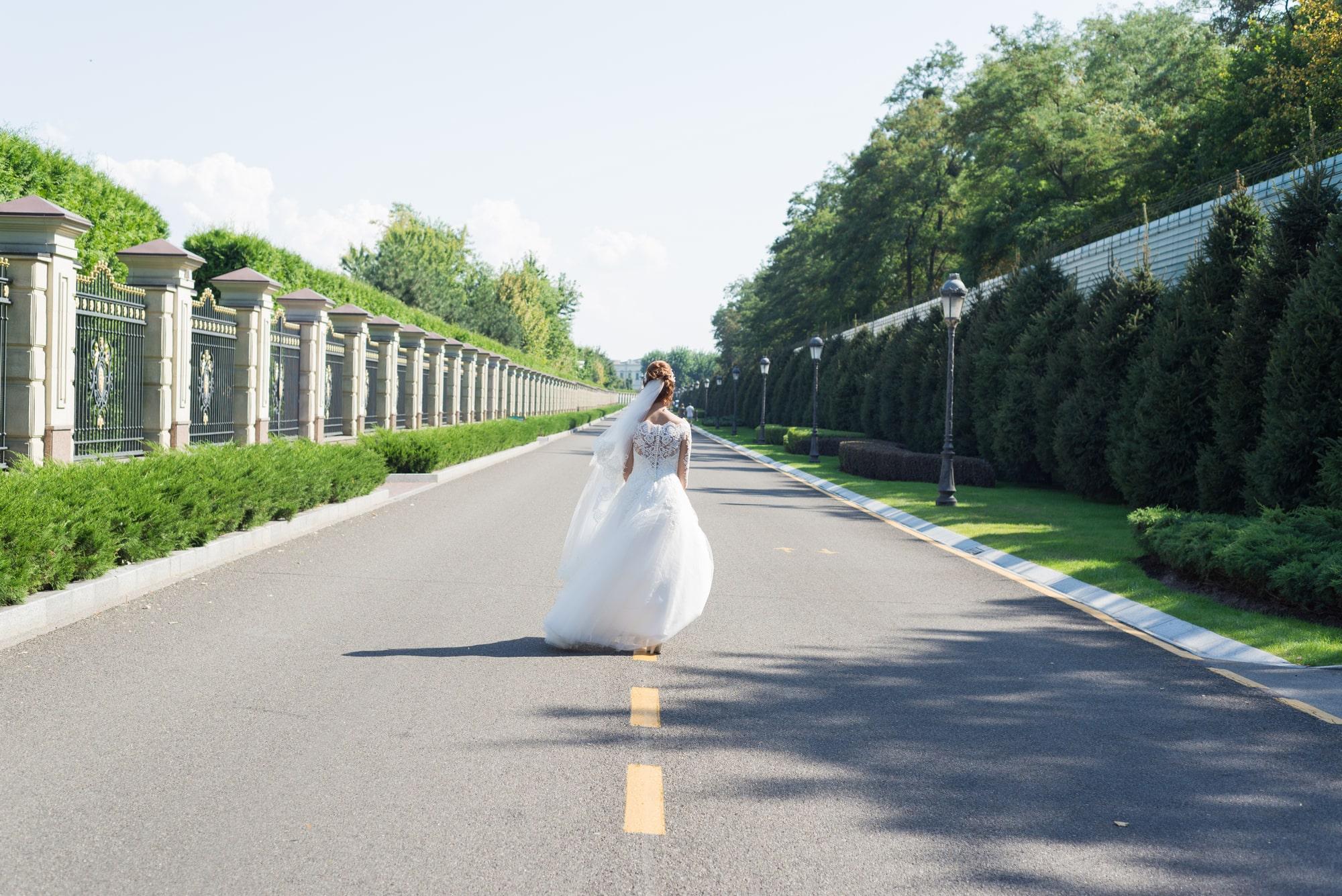 Свадебная фотосъемка в Межигорье - невеста уходит по дороге