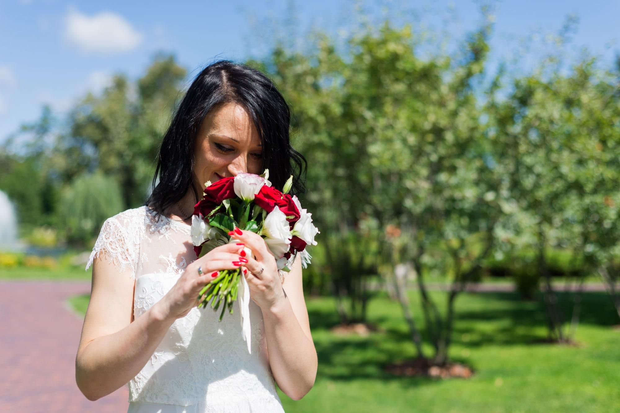 Свадебная фотосъемка в августе - невеста смотрит на букет