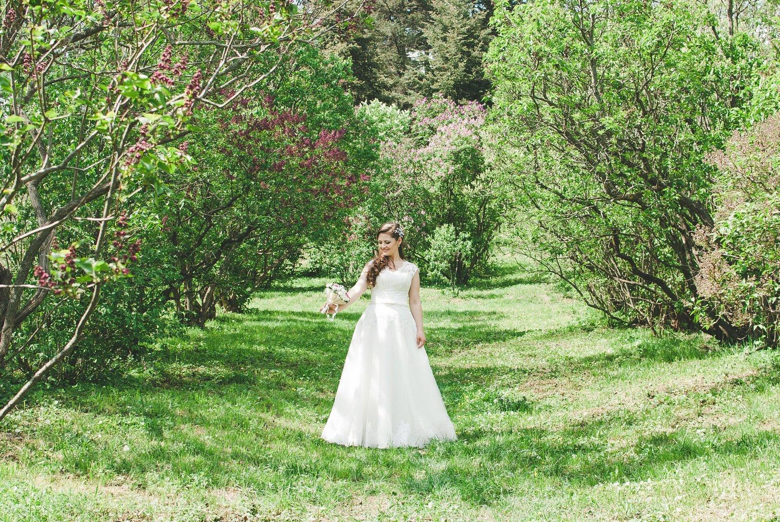 Невеста разглядывает букет в ботсаду - фотограф Женя Лайт