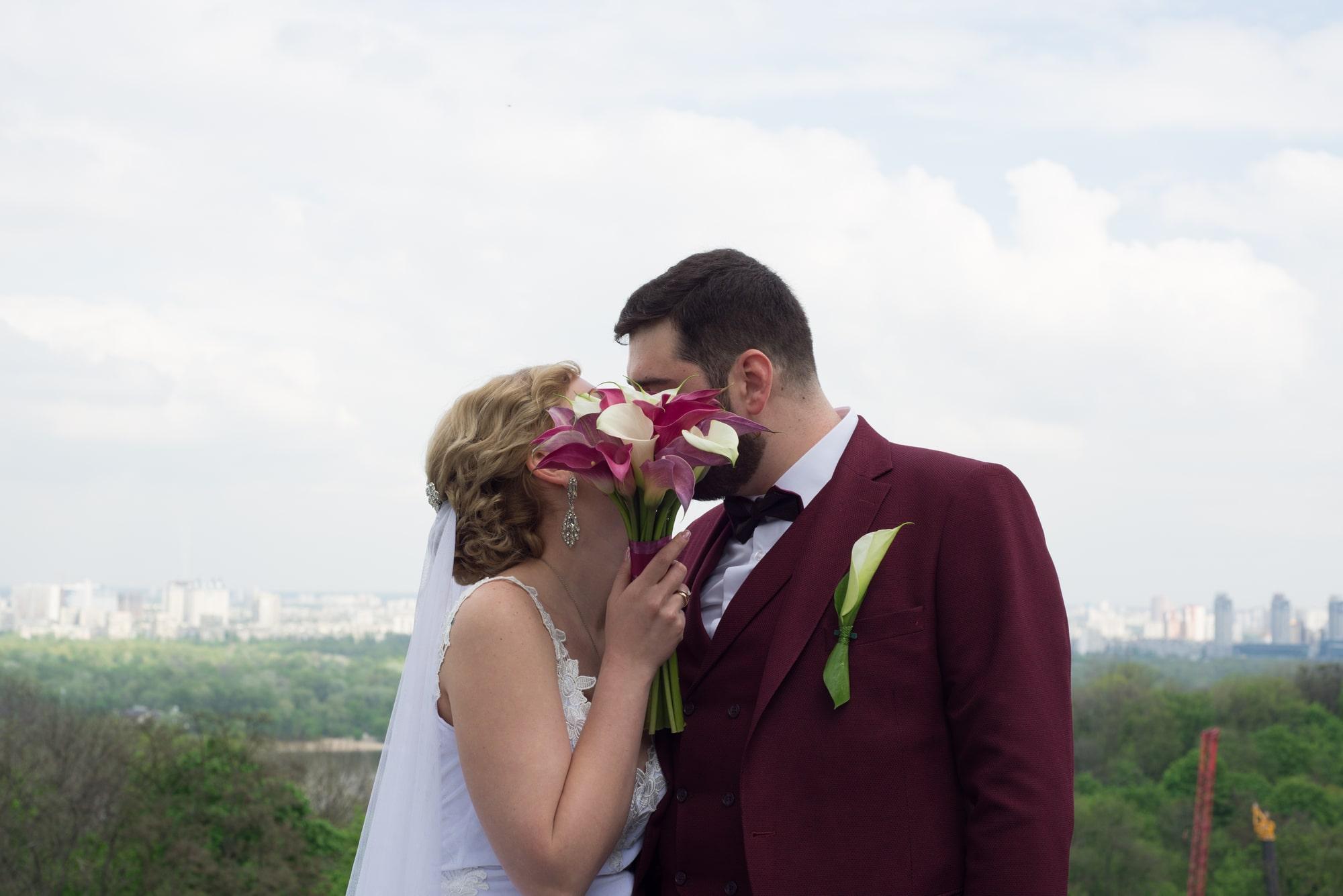 Молодожены закрыли поцелуй букетом - Фотограф Женя Лайт