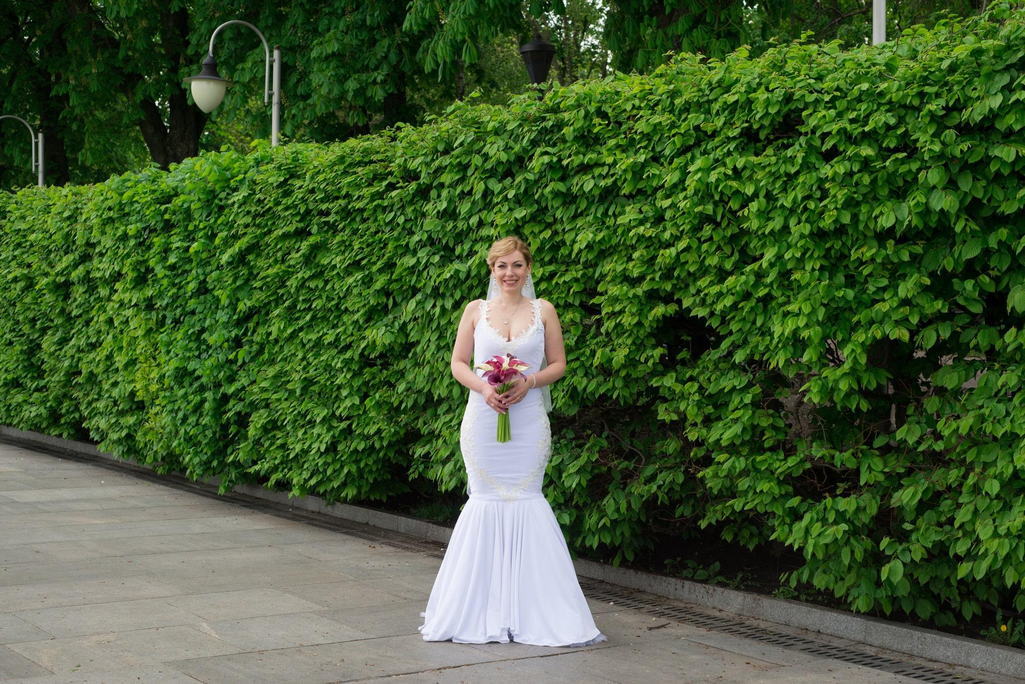 Невеста с букетом фотографируется в парке - Фотограф Женя Лайт