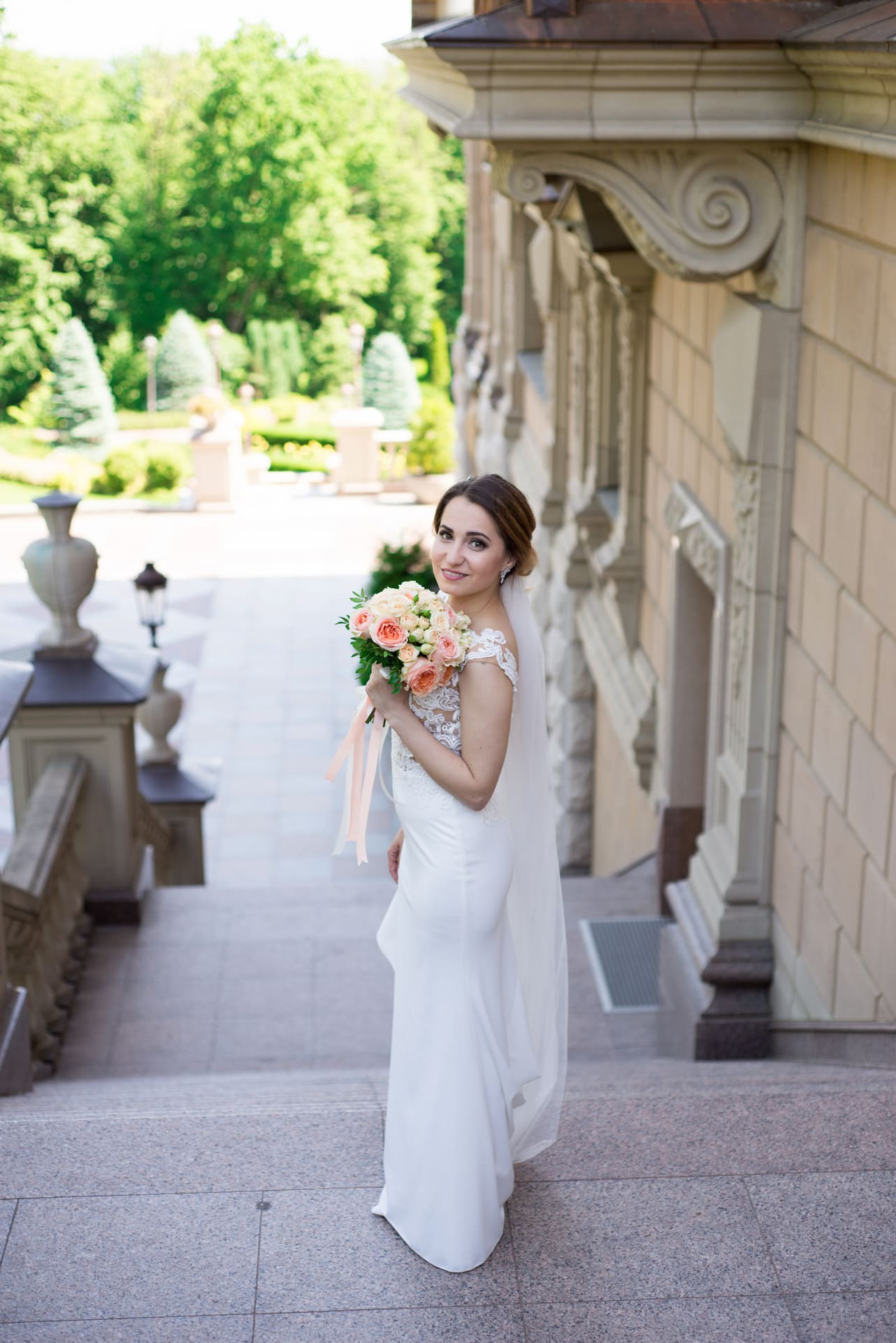 Свадебная фотосессия в Межигорье: Невеста с букетом на ступеньках