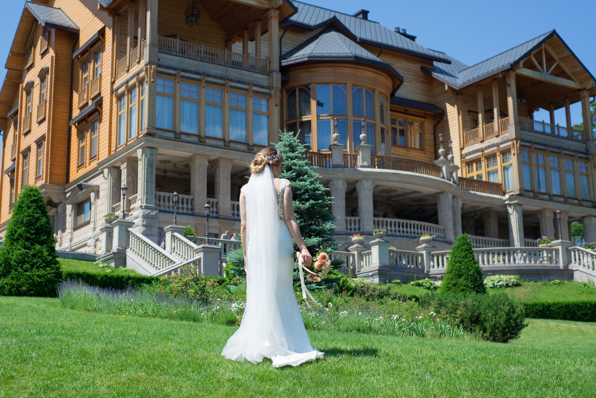 Свадебная фотосессия в Межигорье: Невеста позирует на зеленой лужайке