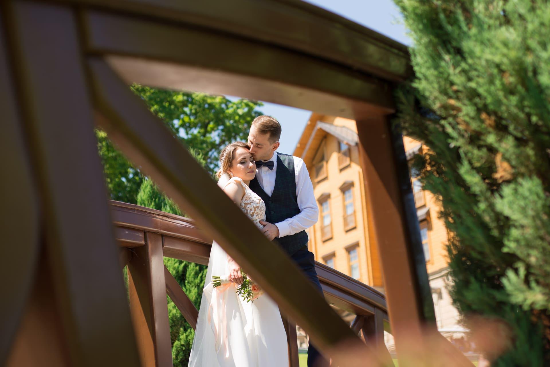 Свадебная фотосессия в Межигорье: Жених и невеста на мостике в парке