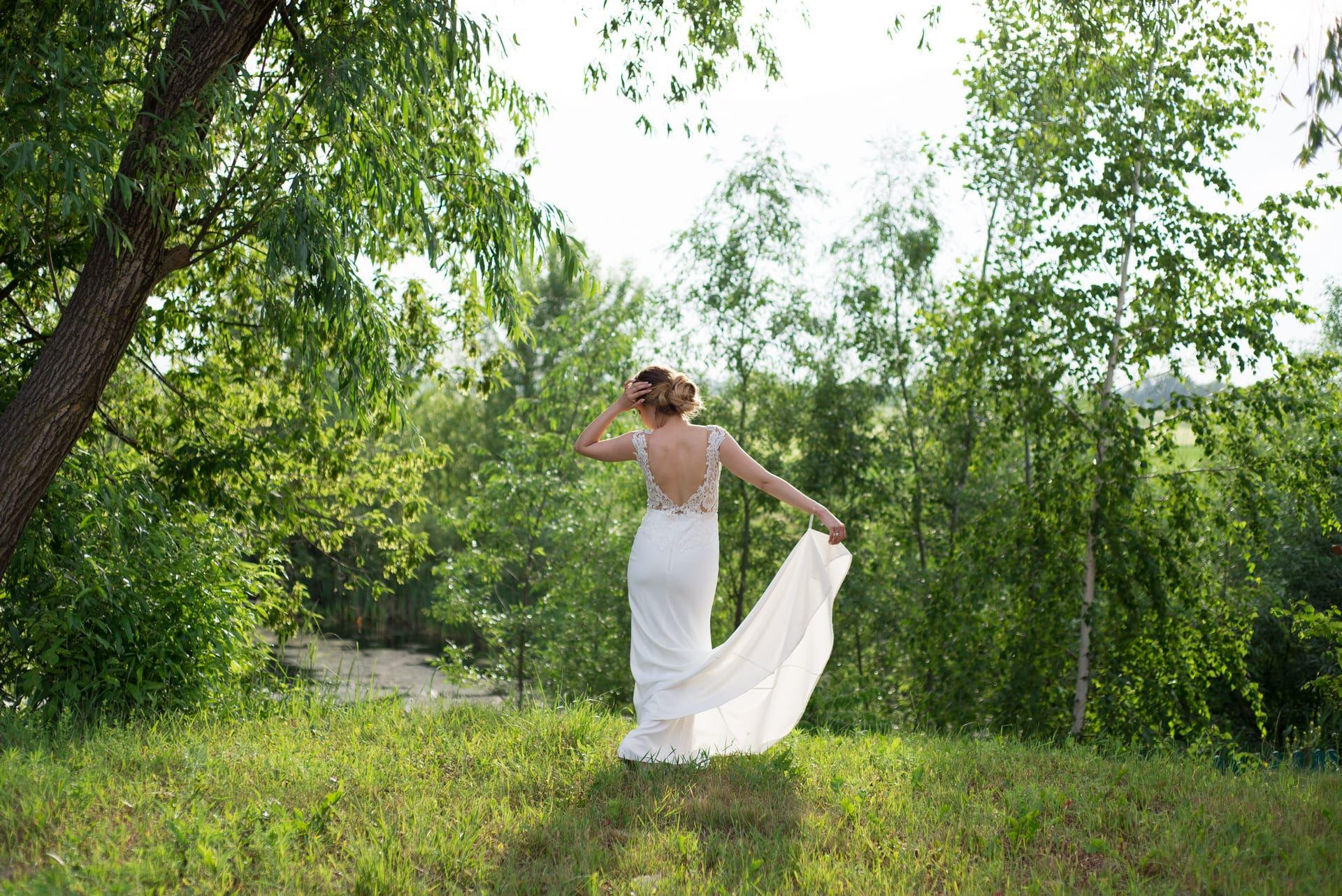 Свадебная фотосессия в Межигорье: Невеста на берегу реки любуется закатом